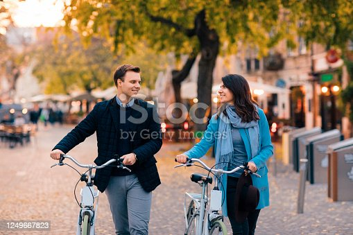 Young couple in love riding a bike on autumn day and looking at each other.