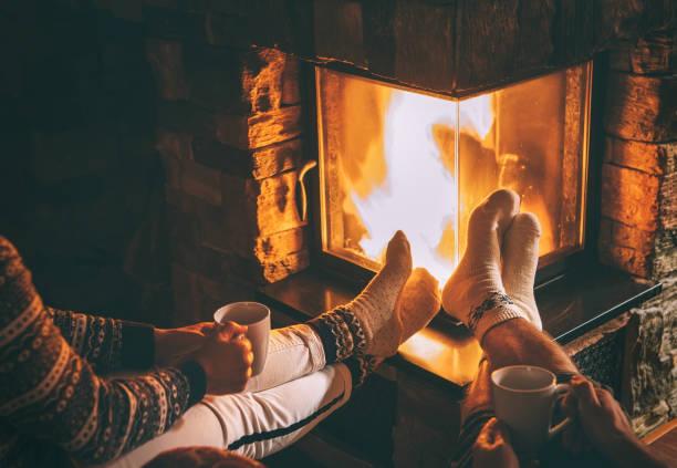 paar in der liebe, in der nähe von kamin sitzen. beine in warmen socken nahaufnahme bild. gemütliche weihnachten zuhause atmosphäre - behaglich stock-fotos und bilder