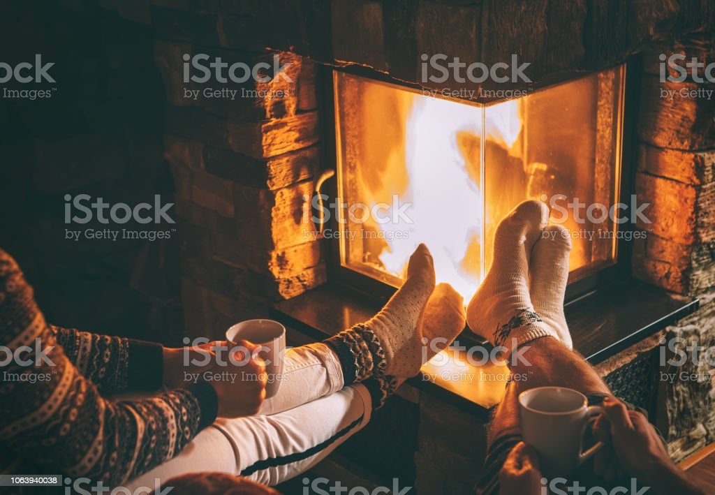 Paar in der Liebe, in der Nähe von Kamin sitzen. Beine in warmen Socken Nahaufnahme Bild. Gemütliche Weihnachten Zuhause Atmosphäre – Foto