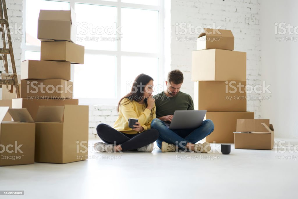 Couple in love sitting near stacked cardboard boxes just relocated to new rent apartments using laptop computer and wireless connection shopping online in web store buying stuff for designing room stock photo