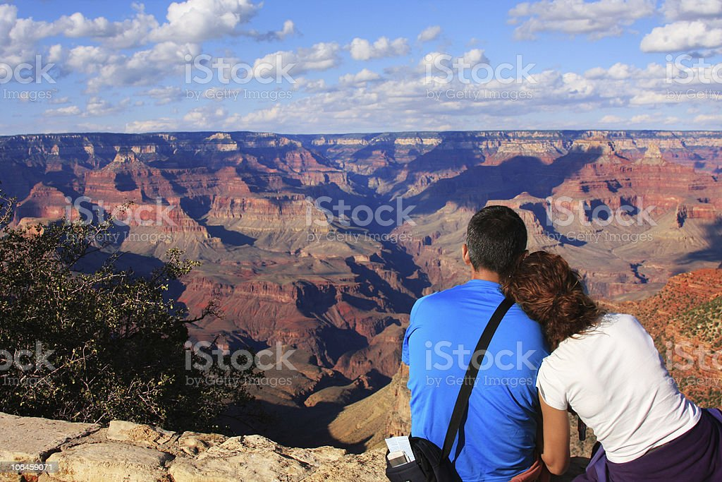 Couple in love sitting on cliff and watching Grand Canyon stock photo