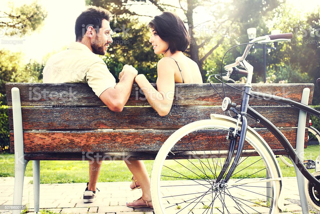 Couple in love sitting together on a bench with bikes stock photo
