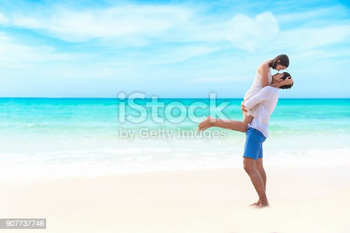 950598260 istock photo Couple in love. Smiling asian young man is holding girlfriend in his arms 907737746