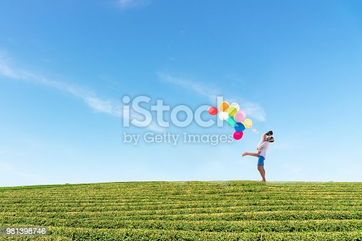 950598260 istock photo Couple in love. Smiling asian young man is holding girlfriend in his arms with multi color balloon minimal 981398746