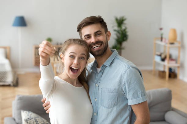 couple in love standing in living room at new house - tenant stock photos and pictures