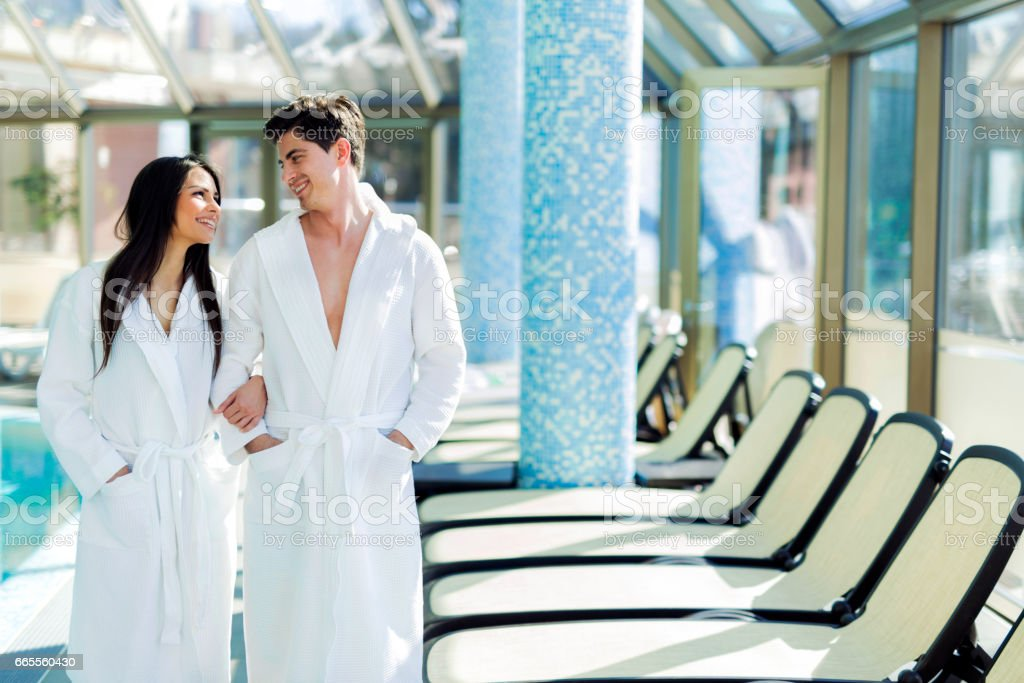 Couple in love standing next to a  pool in a  robe and relaxing ストックフォト