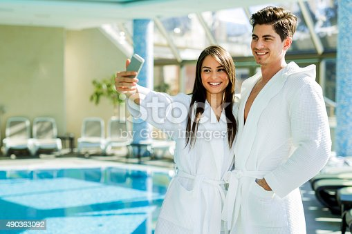 610769340istockphoto Couple in love standing next to a  pool 490363092