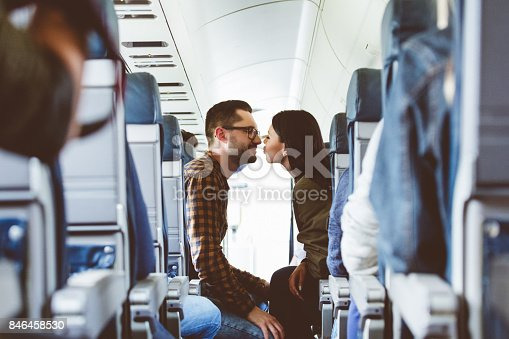 Young couple about to kiss in flight. Couple in love traveling by airplane.