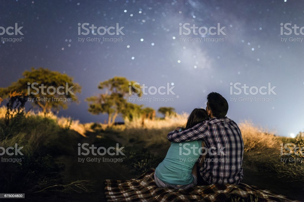 couple in love under stars of Milky Way Galaxy stock photo