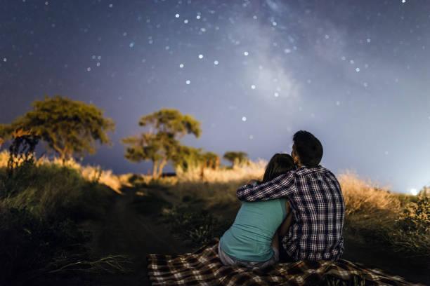 couple amoureux sous les étoiles de la voie lactée - astronomie photos et images de collection