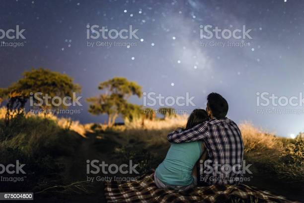Photo of couple in love under stars of Milky Way Galaxy