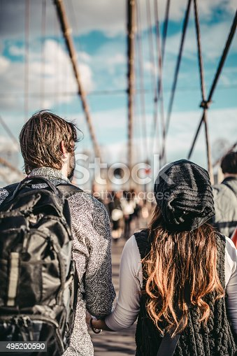 DSLR picture of a couple in love walking hand in hand on the famous Brooklyn Bridge during a beautiful sunny autumn day.