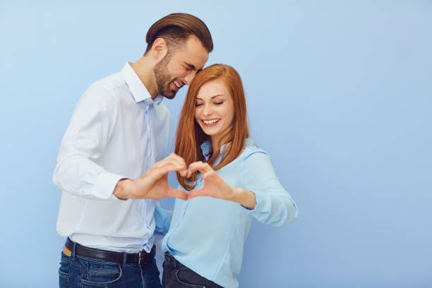 Couple in love with a heart on a blue background. stock photo