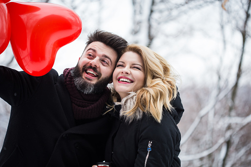 Couple in love with balloons - winter day of St. Valentine