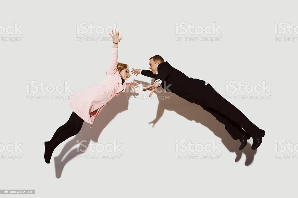 Couple in mid air against white background, side view royalty-free 스톡 사진