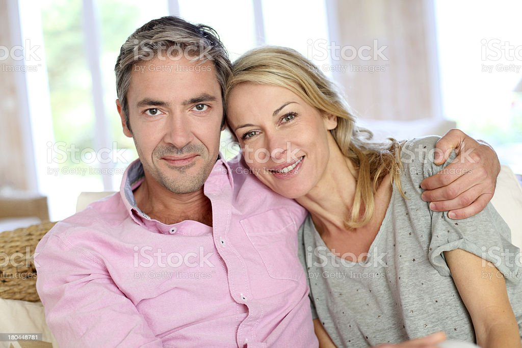 Couple in middle-aged sitting on sofa at home royalty-free stock photo