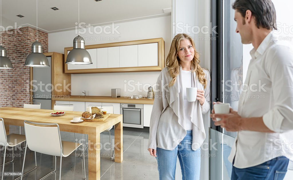 Young couple drinking coffee in a modern kitchen