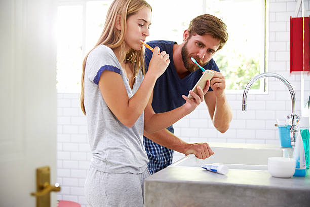 couple in pajamas brushing teeth and using mobile phone - cell phone toilet stockfoto's en -beelden