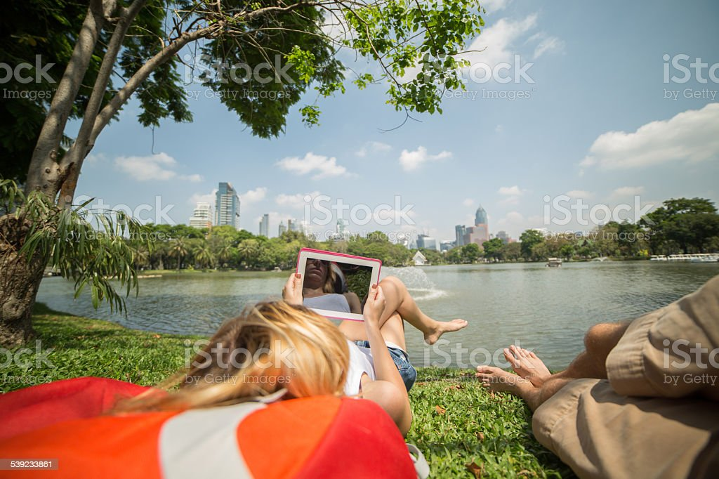 Couple in park relaxing and using a digital tablet royalty-free stock photo