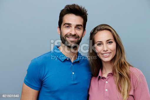 621502402 istock photo Couple in polo shirts smiling for camera 621501540