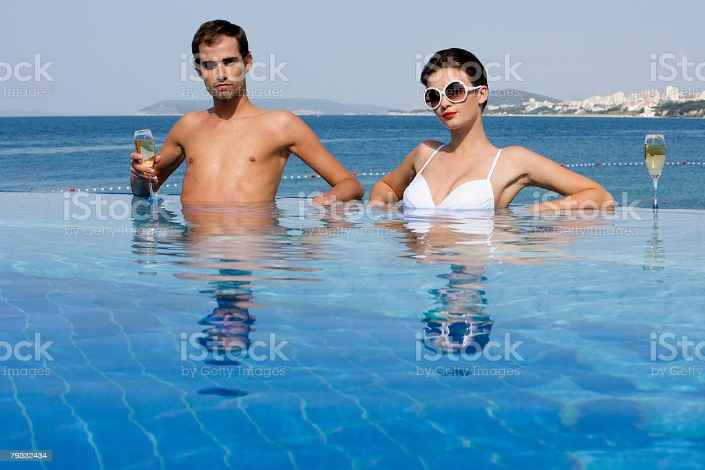 Couple in pool with champagne 免版稅 stock photo