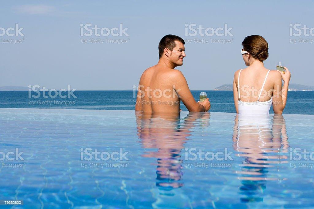 Casal na piscina com Champanhe foto de stock royalty-free