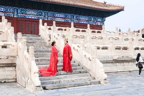 paar in roten kleidern auf stufen der halle für den gottesdienst - hofkleider stock-fotos und bilder