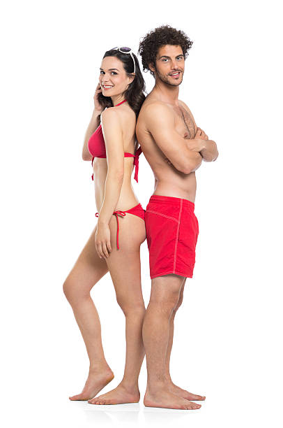 Couple In Red Swimwear Happy Couple In Red Swimwear Standing Isolated On White Background swimwear stock pictures, royalty-free photos & images