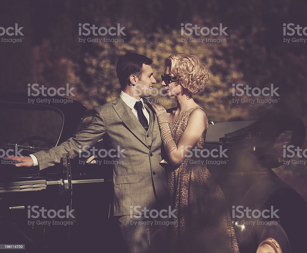 A couple in retro clothing standing with a car outdoors stock photo