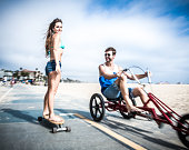 Couple in LA - riding three wheel bicycle and doing skateboarding