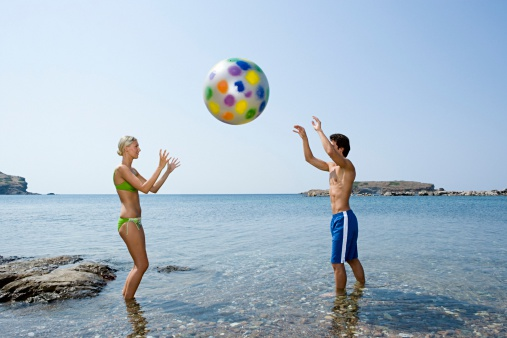 Couple in sea with beachball