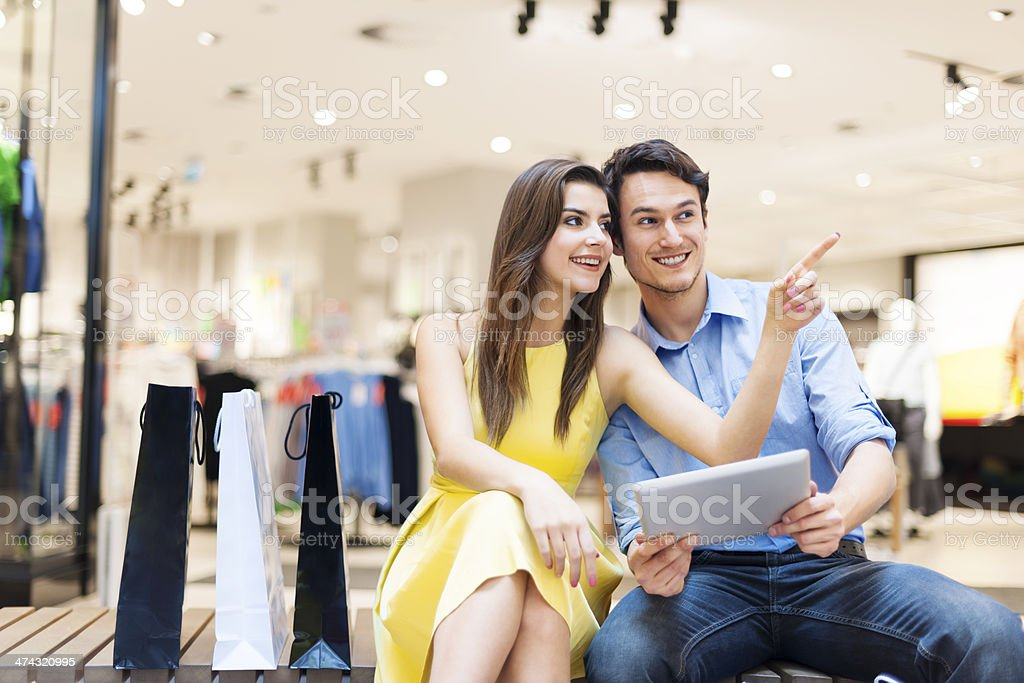 Couple in shopping mall using digital tablet stock photo