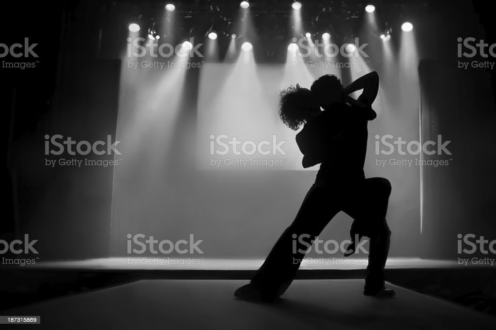 Couple in silhouette dancing on a stage stock photo