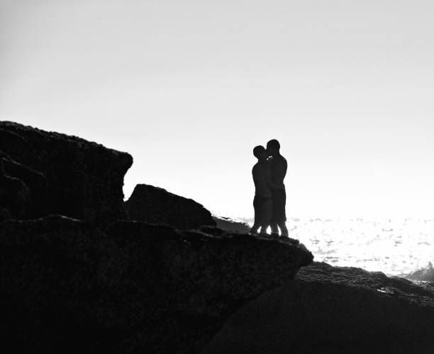 couple in silhouette kissing at seashore stock photo