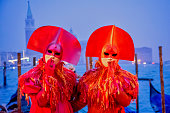 January, 31, 2016, Italy, Venice - Couple in similar red carnival costumes posing at night  by venetian lagoon