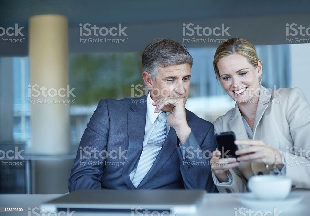 Couple in social clothes looking at a smartphone royalty-free stock photo