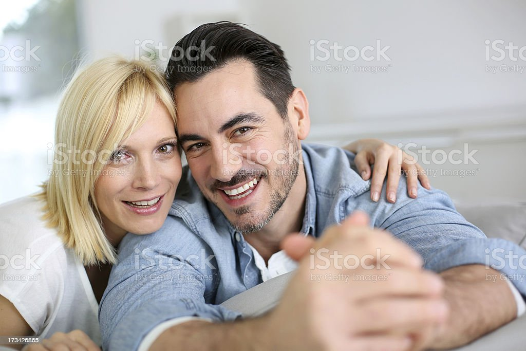 Couple in sofa looking at camera royalty-free stock photo