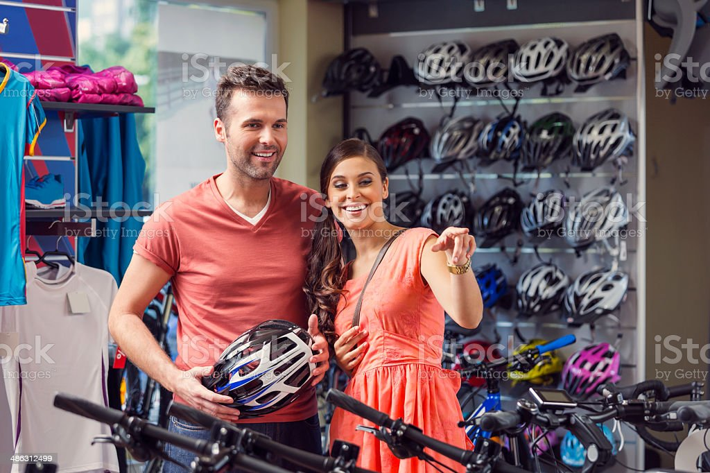 Couple in sports store Couple watching bicycles in a bike store, man holding cycling helmet in hands. Adult Stock Photo
