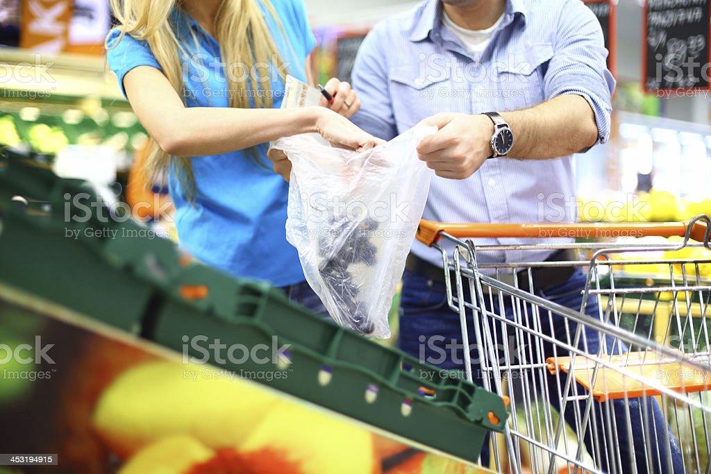 Couple in supermarket buying fruit. stock photo