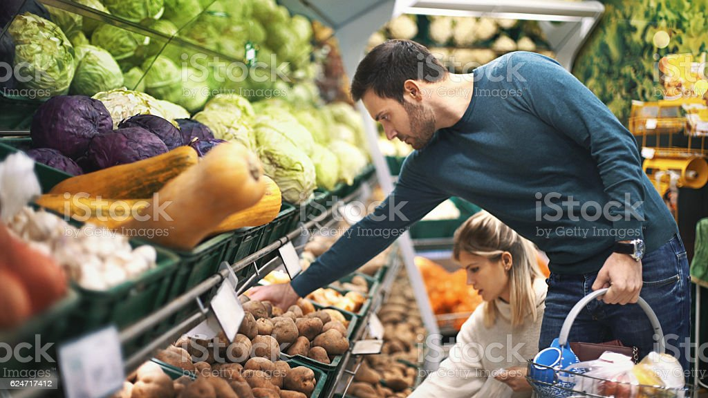 Couple in supermarket buying vegetables. stock photo