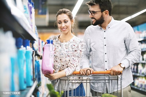 Young attractive couple choosing fabric softener in a supermarket.