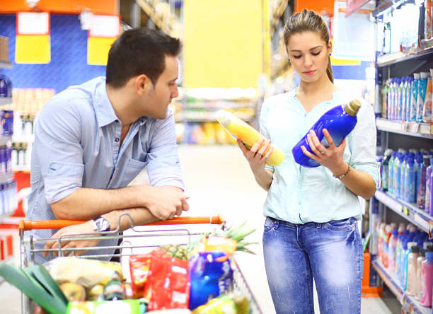 Couple in supermarket. Mid 20's couple in supermarket shopping together. Buying food and household items. She has dark blond hair pulled back with a clip and choosing laundry softener. He's bored and just physically present :) laundry detergent stock pictures, royalty-free photos & images