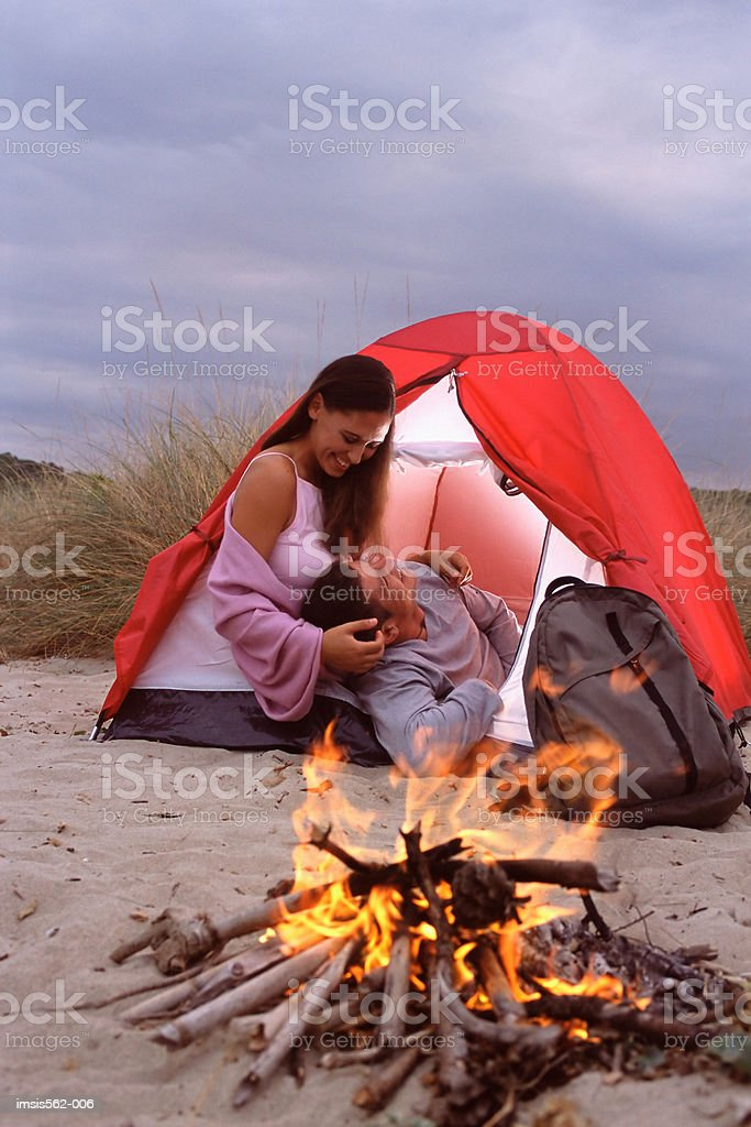 Couple in tent by camp-fire royalty free stockfoto