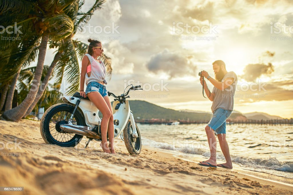 couple in thailand taking photos of each other with motorbike at sunset Стоковые фото Стоковая фотография