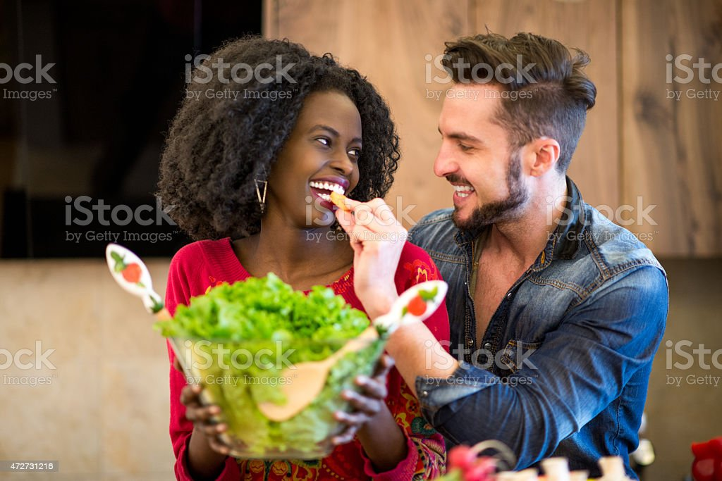 Couple in the kitchen with salad stock photo