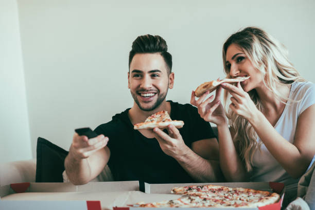 Couple in the living room eating pizza and watching television stock photo