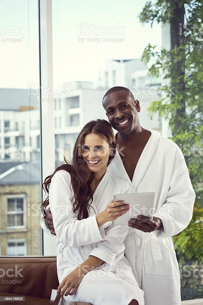 Couple in the morning Friendly afro american man and beautiful brunette wearing white bathrobes standing in their apartment, holding a digital tablet and smiling at the camera. 30-39 Years Stock Photo