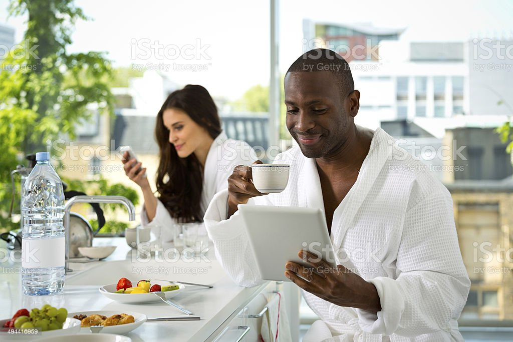 Couple in the morning Afro american man and beautiful brunette wearing white bathrobes having breakfast in their apartment. Focus on the man drinking coffee and using a digital tablet with a woman using smart phone in the background. 30-39 Years Stock Photo