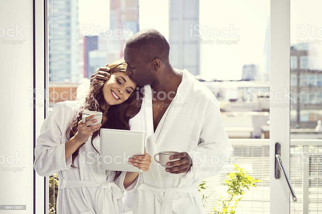 Couple in the morning Afro american man and beautiful brunette wearing white bathrobes standing with cups onf coffee and digital tablet in their aparment in the morning, man kissing a woman. 30-39 Years Stock Photo