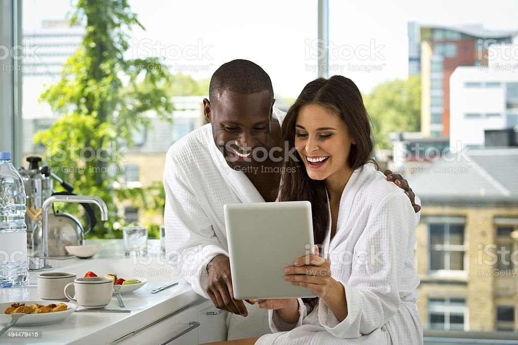 Couple in the morning Afro american man and beautiful brunette wearing white bathrobes sitting in the kitchen in the morning and using a digital tablet together.  30-39 Years Stock Photo